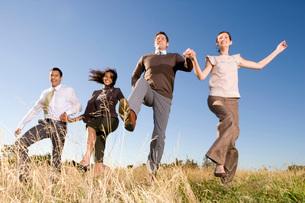 people skipping in fieldの写真素材 [FYI01994147]