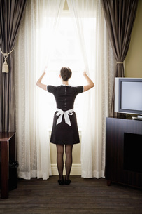 Maid looking out windowの写真素材 [FYI01994198]