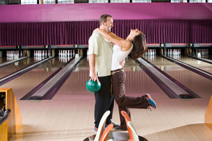 Couple kissing in bowling alleyの写真素材 [FYI01994209]