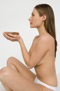 nude woman holding a bowlの写真素材 [FYI01994265]