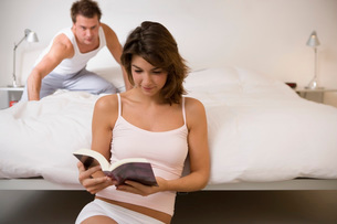 Husband sneaking up on wife reading bookの写真素材 [FYI01994288]