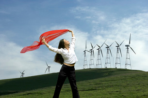 Woman holding scarf at a wind farmの写真素材 [FYI01994335]