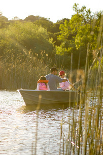 Family fishing in boat on lakeの写真素材 [FYI01994433]