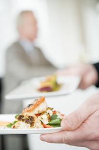 Plates of food in waiter's handsの写真素材 [FYI01994443]
