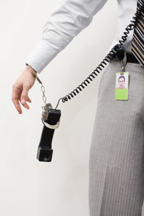 man handcuffed to telephone receiverの写真素材 [FYI01994478]