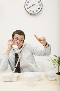 Businessman talking on two telephonesの写真素材 [FYI01994504]