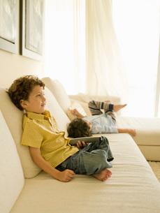 Children relaxing on sofaの写真素材 [FYI01994558]