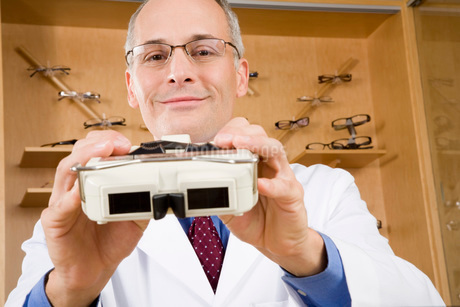 Male optician holding diagnostic toolの写真素材 [FYI01994654]