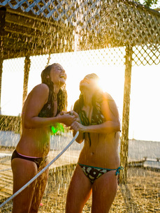 Teenage girls in bikinis playing in hoseの写真素材 [FYI01994677]
