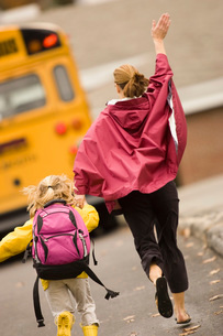 Mother and daughter running for busの写真素材 [FYI01994694]