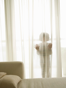 Child hiding behind sheer curtainsの写真素材 [FYI01994778]
