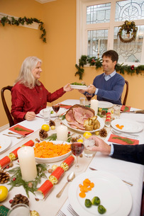 Family passing food around dinner tableの写真素材 [FYI01994798]