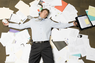 Businessman laying on pile of paperworkの写真素材 [FYI01994860]