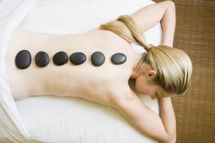 Woman receiving spa stone treatmentの写真素材 [FYI01994874]