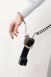man handcuffed to telephone receiverの写真素材 [FYI01994875]