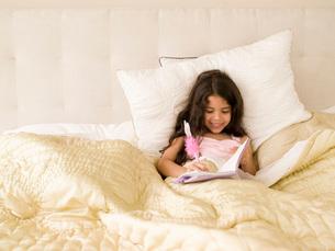 Girl writing in diary in bedの写真素材 [FYI01994893]
