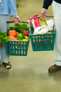 People holding grocery basketsの写真素材 [FYI01994919]