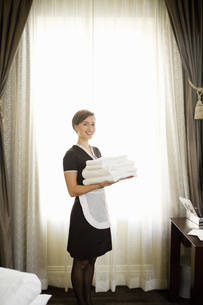 Maid holding stack of towelsの写真素材 [FYI01994942]
