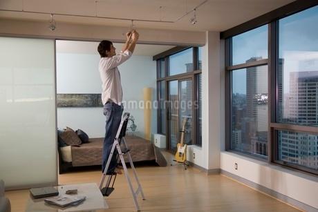 Young man replacing light bulbの写真素材 [FYI01994980]