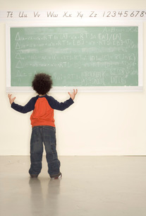 Child frustrated looking at blackboardの写真素材 [FYI01994983]