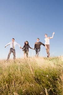 people skipping in fieldの写真素材 [FYI01994994]