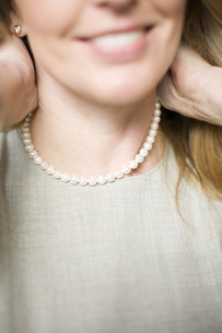 Woman fastening pearl necklaceの写真素材 [FYI01995036]
