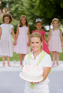 Mother holding daughters birthday cakeの写真素材 [FYI01995041]