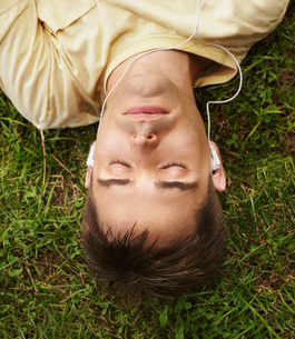 Man listening to earphones while layingの写真素材 [FYI01995048]