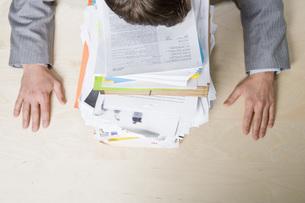man resting head on stack of paperworkの写真素材 [FYI01995057]