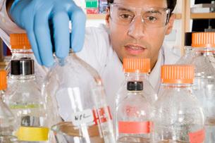 Male scientist reaching for bottleの写真素材 [FYI01995086]