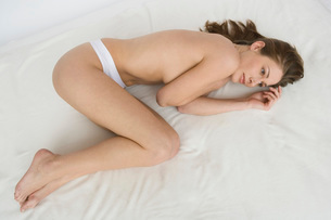 Nude woman laying on bedの写真素材 [FYI01995088]