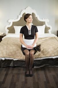 Maid sitting on edge of bedの写真素材 [FYI01995145]