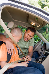 Father buckling his son into the carの写真素材 [FYI01995168]