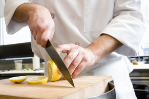Male chef slicing lemonの写真素材 [FYI01995196]