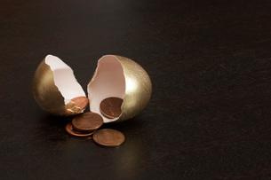 Cracked golden egg containing penniesの写真素材 [FYI01995202]