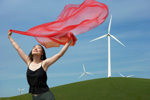 Woman holding scarf at a wind farmの写真素材 [FYI01995244]
