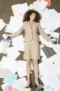 woman laying on pile of paperworkの写真素材 [FYI01995277]