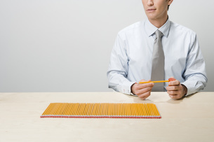 Businessman next to row of pencilsの写真素材 [FYI01995300]