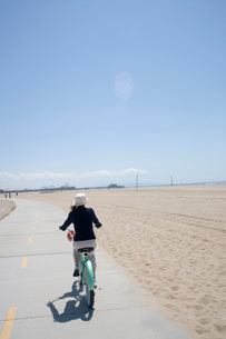 Woman riding bicycle on beachの写真素材 [FYI01995349]