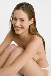 Nude woman hugging her kneesの写真素材 [FYI01995390]
