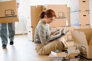 Woman looking through books as she packsの写真素材 [FYI01995404]