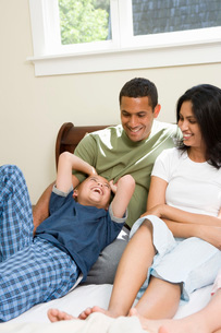 Family relaxing on bedの写真素材 [FYI01995418]