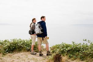 Couple on cliff overlooking waterの写真素材 [FYI01995443]