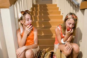 Twin girls eating applesの写真素材 [FYI01995501]