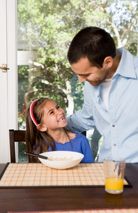 Father and daughter eating breakfastの写真素材 [FYI01995529]
