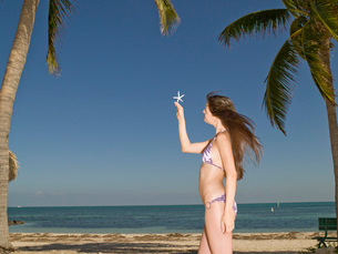 Woman holding a dried starfish on beachの写真素材 [FYI01995545]