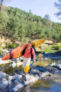 Woman carrying kayak acrossの写真素材 [FYI01995550]