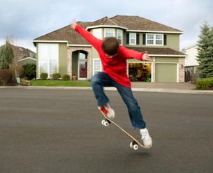 Boy skateboarding on residential streetの写真素材 [FYI01995552]