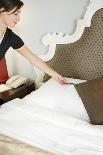 Maid putting mint on pillowの写真素材 [FYI01995557]