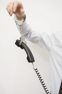 man handcuffed to telephone receiverの写真素材 [FYI01995649]